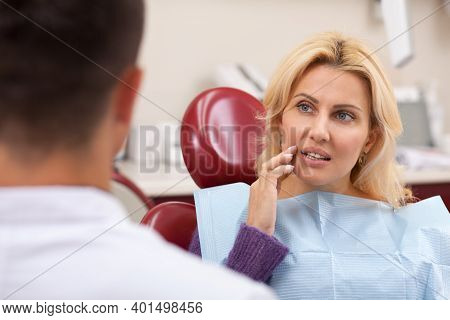 Gorgeous Mature Woman Talking To Her Dentist Before Receiving Medical Treatment For Her Toothache. B