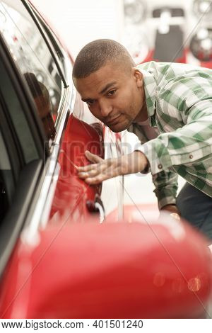 Handsome Young African Man Examining Cars At The Dealership, Touching Door Of An Auto, Checking Out