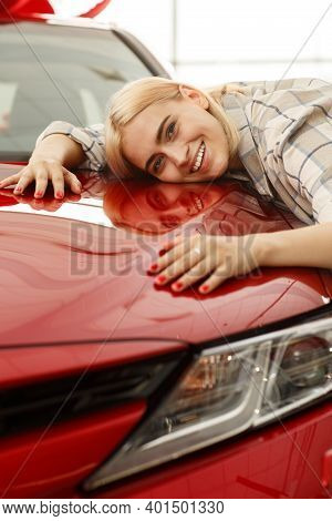 Vertical Shot Of A Beautiful Young Woman Embracing Her New Automobile At The Dealership. Gorgeous Fe