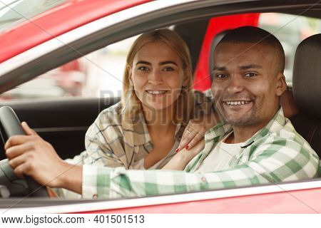 Happy Young Lovely Couple Smiling To The Camera Sitting In Their New Automobile. Handsome African Ma