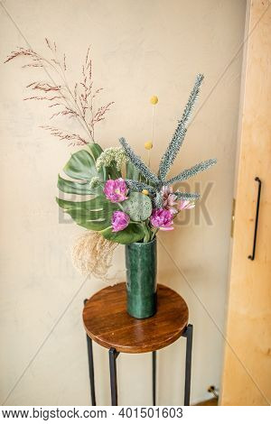 Composition Of Fresh Flowers In A Green Vase On A Beige Wall Background. Bouquet Of Nobilis, Monster