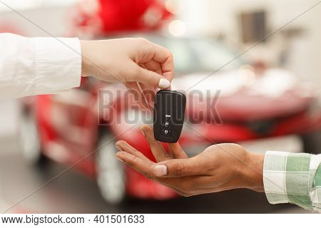 Cropped Close Up Of A Male Customer Receiving Car Keys From Salesperson After Buying New Automobile