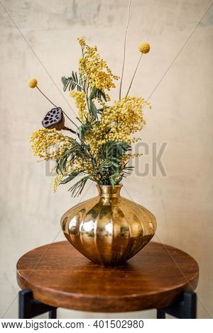 Composition Of Fresh Flowers And Herbs In A Gold Vase On A Beige Wall Background. Bouquet Of Acacia,