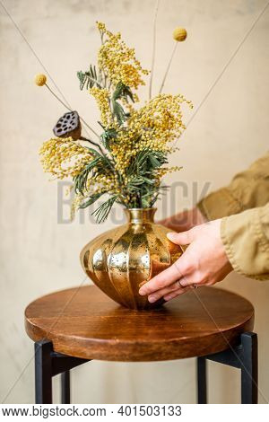 Female Decoarting Home With Composition Of Fresh Flowers And Herbs In A Gold Vase On A Beige Wall Ba