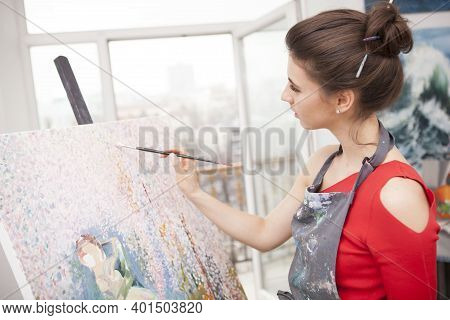 Young Woman Enjoying Working On Her Painting At Art Studio, Copy Space