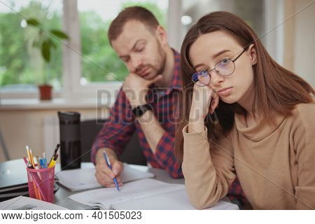 Teenage Girl Looking Bored While Studying With A Tutor In Class, Copy Space. Tired Teen Female Stude