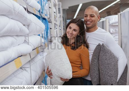 Lovely Multiracial Couple Buying New Pillows At Home Goods Store. Charming Woman Shopping For Beddin