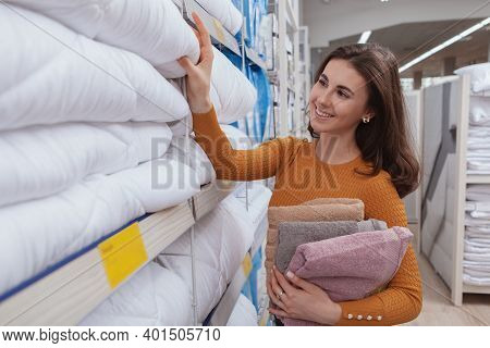 Young Beautiful Happy Woman Choosing A New Blanket From The Shelf At Furnishings Store