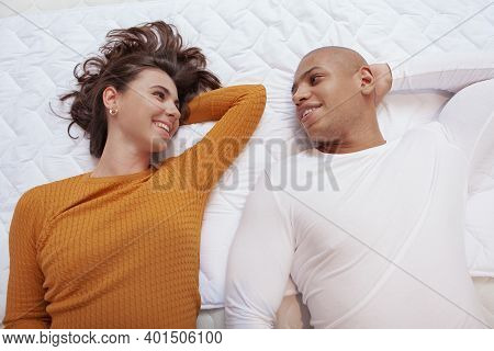 Top View Shot Of A Happy Multiethnic Couple Lying On Orthopedic Bed Together. Young Couple Smiling A