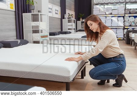 Full Length Shot Of A Lovely Young Woman Examining Orthopedic Mattress At Furniture Store, Copy Spac