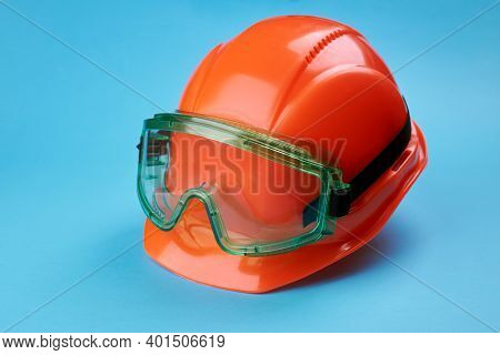 Orange Protective Helmet And Safety Glasses Near It On A Bright Blue Background. Protective Workwear