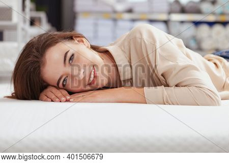 Close Up Of A Happy Beautiful Woman Trying Orthopedic Bed At Furniture Store. Cheerful Female Custom