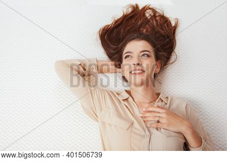 Top View Shot Of A Happy Woman Smiling, Lying On Orthopedic Mattress, Copy Space. Healthy Sleep, Rel
