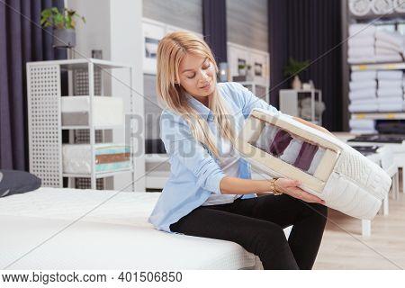 Attractive Female Customer Examining Orthopedic Mattress Sample, Shopping For Bedroom Furniture