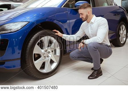Full Length Shot Of A Handsome Elegant Man Examining Wheels And Tires Of A Car He Is Buying At The D
