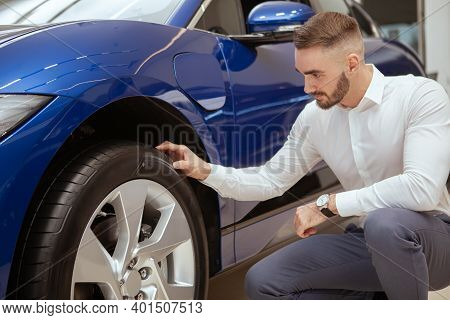 Handsome Bearded Man Examining Tires On A New Car On Sale At The Dealership