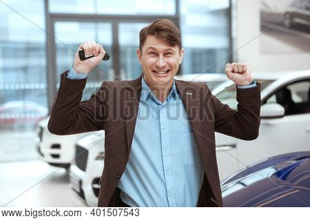 Happy Excited Man Celebrating Buying New Car, Holdidng Car Keys. Mature Man Winning New Automobile