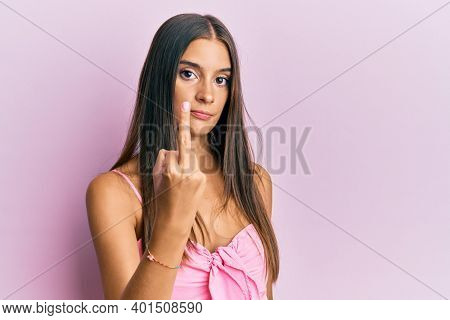 Young hispanic woman wearing casual style with sleeveless shirt showing middle finger, impolite and rude fuck off expression