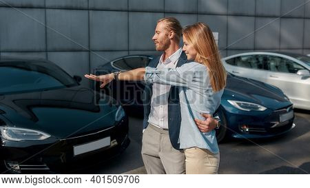 Happy Young Caucasian Woman Pointing At Car While Standing Beside Young Businessman In Luxury Auto S