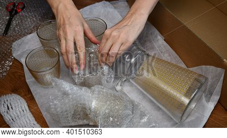 Woman Hands Pack Up Fragile Glassware Into Wrapping Bubble Plastic In Preparation To Move In New Hom