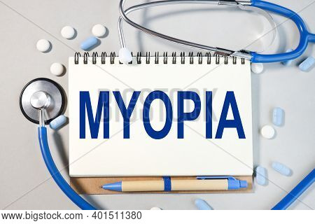 Myopia, Text On White Paper On Gray Background Near Stethoscope. Medetsyna Concept