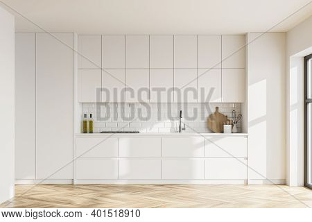 Interior Of Modern Kitchen With White Walls, Wooden Floor, White Cupboards And Built In Sink And Coo