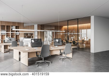 Corner Of Modern Open Space Office With White And Wooden Walls, Concrete Floor And Rows Of Computer