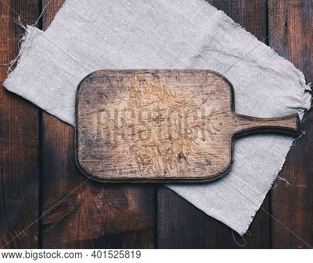 Old Brown Rectangular Wooden Kitchen Cutting Board And Gray Linen Napkin On The Table, Top View