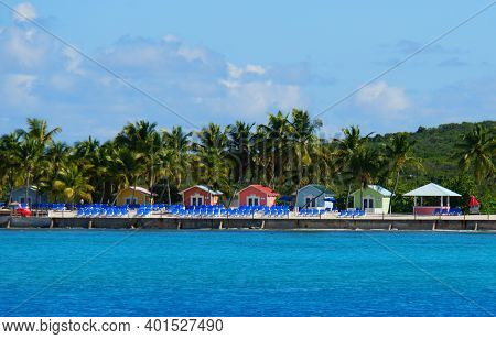 The Distance View Of Beach Chairs In Front Of Colorful Bungalows On The Island Of Princess Cays, Bah