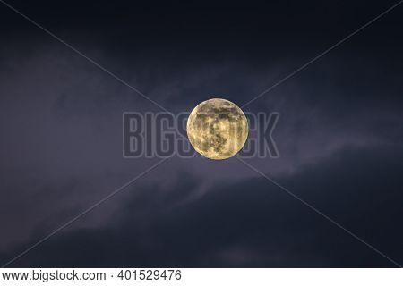 Full Moon December 2020, The Last Full Moon Of The Decade, Rising Through A Cloudy Sky At Dusk