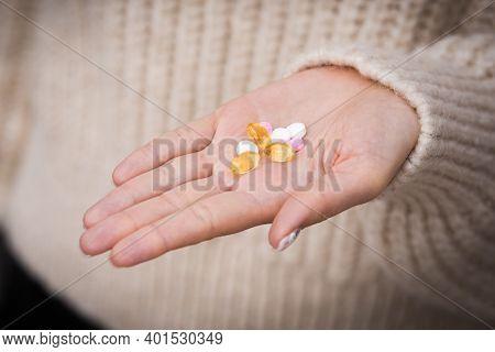 Close Up Of Woman Hand With Vitamins, Minerals And Supplements For Vegans. B12, D3, K2
