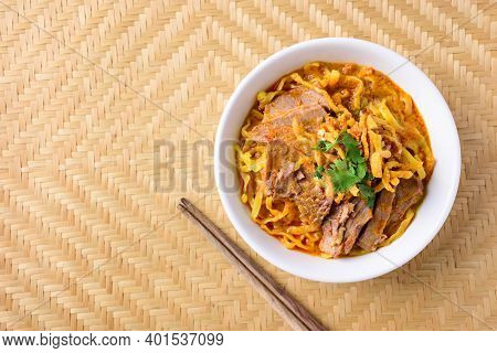 Northern Thai Food (khao Soi), Spicy Curry Noodles Soup With Beef In A Bowl And Chopsticks, Top View