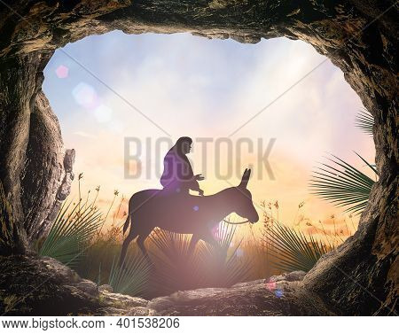 Palm Sunday Concept: Silhouette Jesus Christ Riding Donkey With Tomb Stone On Meadow Sunset Backgrou