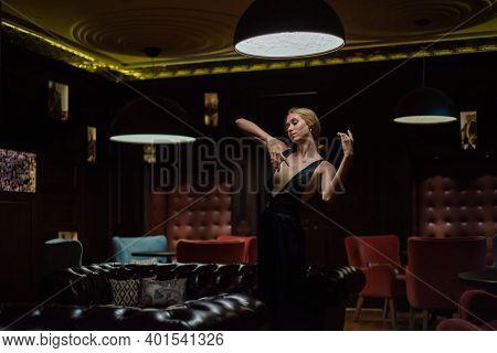 A Graceful Ballerina In A Black Dress Posing In A Restaurant. Beautiful Elegant Woman Dancing In A D