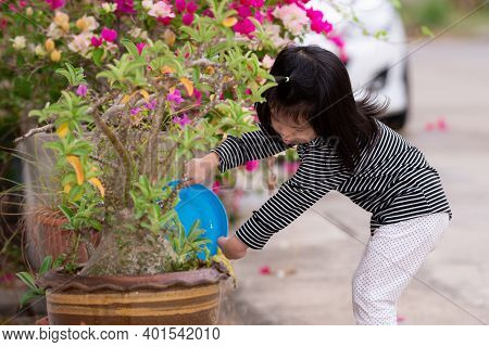 Girl Watering The Trees In Front Of House. Child Help To Lighten Work Of Their Parents. Assign Small