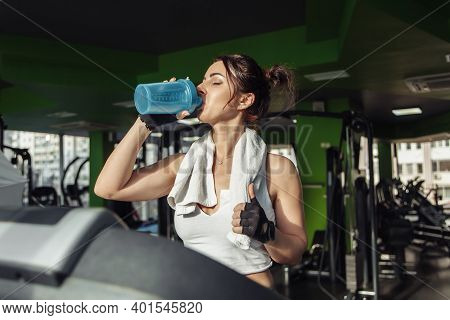 Young Fit Woman With A Towel On Her Shoulders Drinks Water On A Treadmill. Weight Loss Concept, Aero
