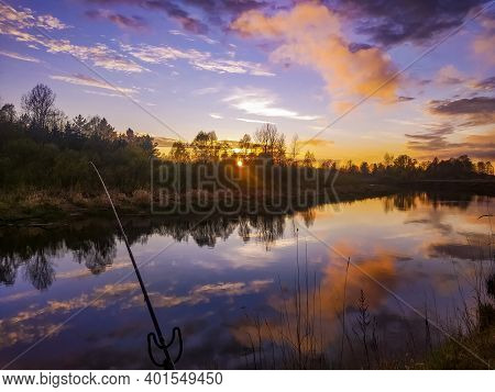 Angler Catches Fish At Sunset For The Forest