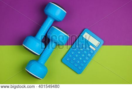 Fitness, Weight Loss Still Life. Calorie Counting. Calculator And Dumbbells On Green Purple Backgrou