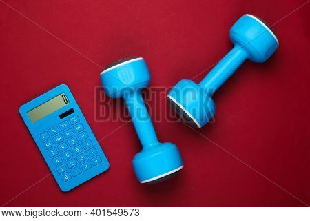 Fitness, Weight Loss Still Life. Calorie Counting. Calculator And Dumbbells On Red Background. Minim