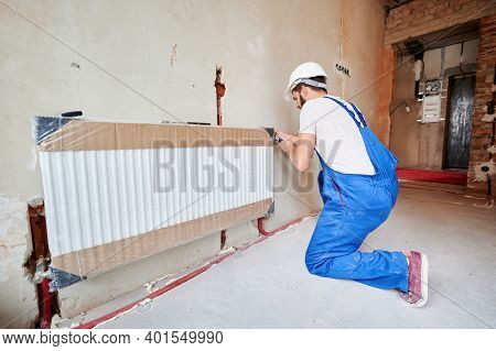 Man In Work Overalls Using Wrench While Installing Heating Radiator In Room. Young Plumber Installin