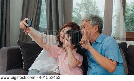 Asian Grandparents Selfie With Granddaughter At Home. Senior Chinese, Grandpa And Grandma Happy Spen