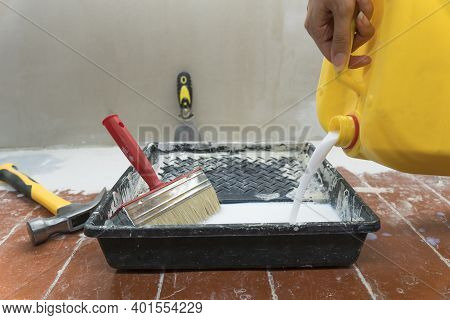 A Construction Worker Pours Paint Or Construction Mix Into A Tray. Work As A Builder Or Handyman In