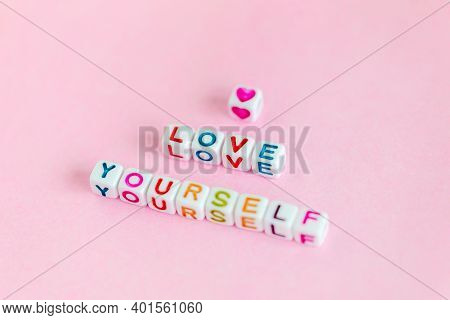 Quote Love Yourself Made Out Of Beads On Pastel Pink Background