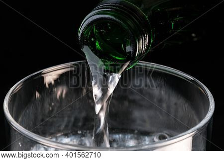 Pure Carbonated Water Pouring From A Bottle Into A Transparent Glass On A Black Background Close-up