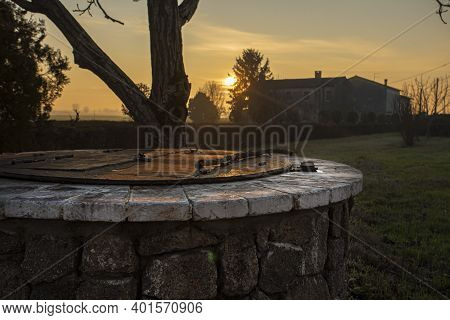 Water Well Immersed In A Countryside Landscape At Sunset Time