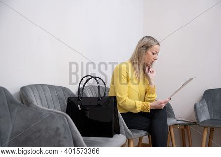 Blond Woman In A Yellow Blouse Getting Ready For A Job Interview.