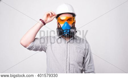 Young Bearded Engineer Wearing A Helmet, Protective Glasses And A Respirator Is Looking At The Camer