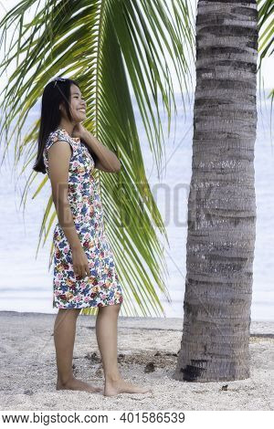 Young Attractive Girl Standing At The Palm Tree
