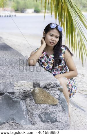 Young Indonesian Girl With Sunglasses Sitting At A Stone Wall