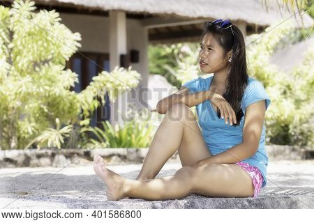 Young Indonesian Girl With Sunglasses Sitting  On A Stone Wall